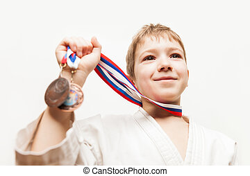 Smiling karate champion child boy gesturing for victory...