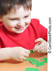 Smiling kid assembling green puzzles - Little smiling kid in...
