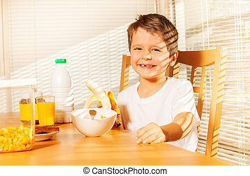 Smiling kid boy holding banana in the kitchen