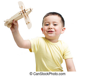 smiling kid boy playing with wooden airplane toy