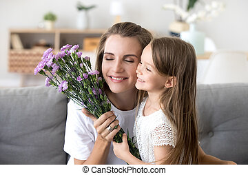 Smiling kid daughter giving flowers congratulating mom with moth
