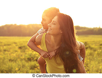 Smiling kid girl embracing her happy enjoying mother on the back on sunset bright summer background. Closeup portrait.