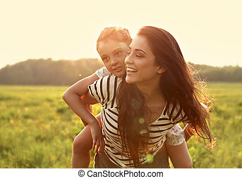 Smiling kid girl laughing on the happy enjoying mother back on sunset bright summer background. Closeup portrait.