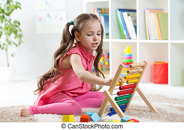 smiling kid girl playing with counter toy