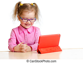 smiling kid in glasses looking at mini tablet pc screen...