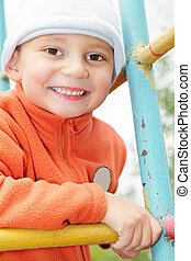 Smiling kid in orange on climbing staircase