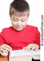 Smiling kid in red reading book at desk