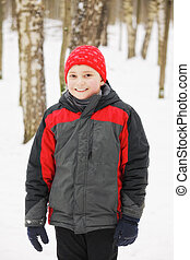 Smiling kid in winter forest