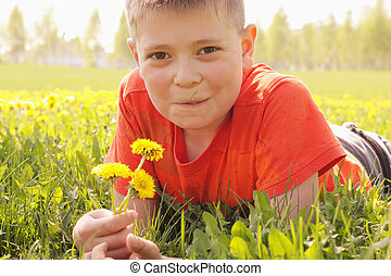 Smiling kid on grass with dandelions