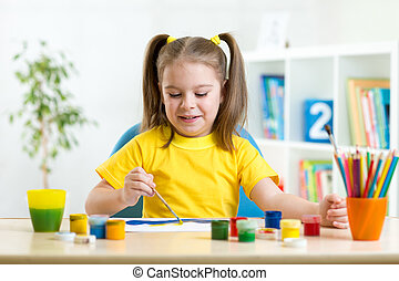 smiling kid painting at home