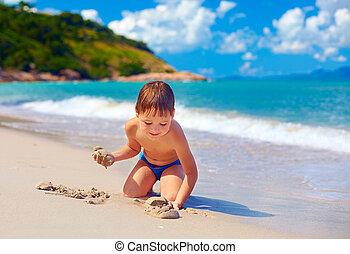 smiling kid playing in sand on tropical island beach
