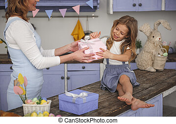 Smiling kid receiving gift from mom
