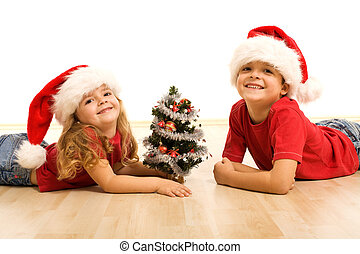 Smiling kids laying on the floor at christmas time - Happy ...