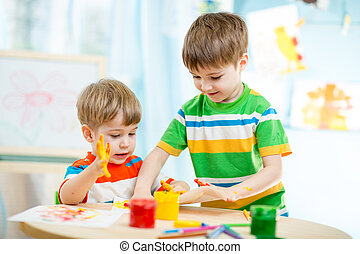 smiling kids play and paint at home or kindergarten or...
