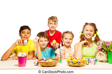 Smiling kids together holding Eastern eggs