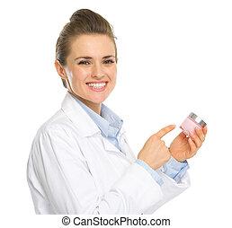 Smiling kosmetist woman pointing on creme