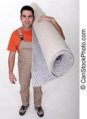 Smiling laborer carrying carpet