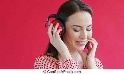 Charming young woman in modern headphones smiling and looking at camera while standing on red background and listening to music