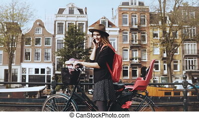 Smiling lady talking on the phone, cycling away. Young...
