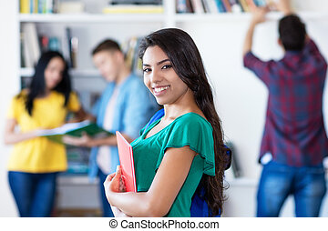 Smiling latin american female student with group of students at library of university