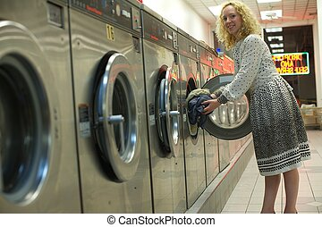 laundromat girl - smiling laundromat girl inserting clothes ...