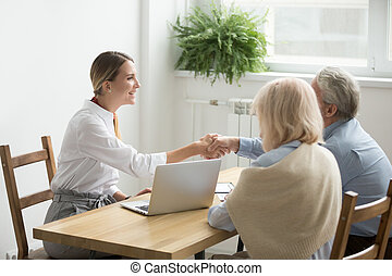 Smiling lawyer or financial advisor handshaking senior couple at