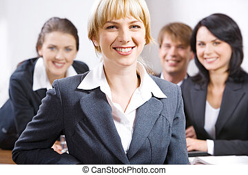 Portrait of smiling female leader on the background of her business team