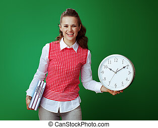 smiling learner woman with textbooks showing white round clock
