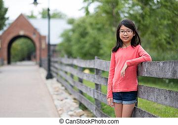 Smiling little Asian girl standing in the park