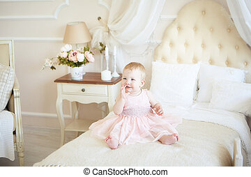 smiling little baby girl in pink dress on the bed