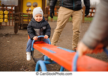 Smiling little boy dressed in warm jacket and hat riding on the swing