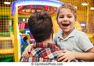 Smiling little boy having fun with his dad