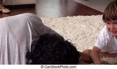 Smiling little boy having fun with his father lying down on floor