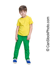 Smiling little boy in a yellow shirt stands