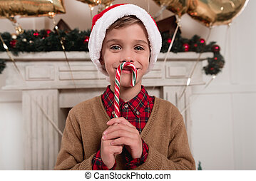 boy in santa hat with candy cane