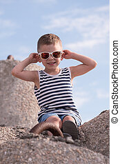 smiling little boy in sunglasses and vest sitting on concrete breakwater