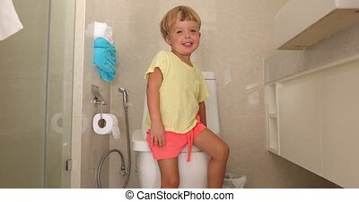 Smiling little boy in toilet - Funny happy child sitting on...
