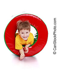 Smiling little boy looks out of a large pipe