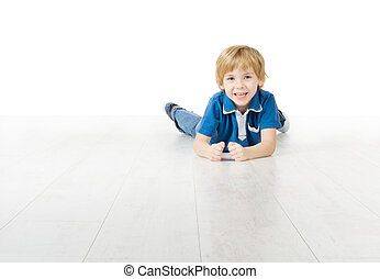 Smiling little boy lying down on floor
