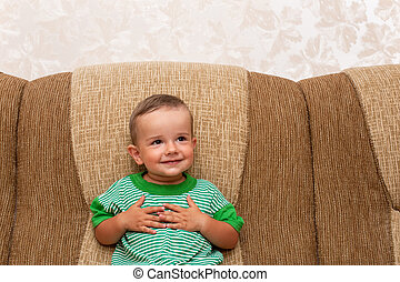 Smiling little boy on the sofa