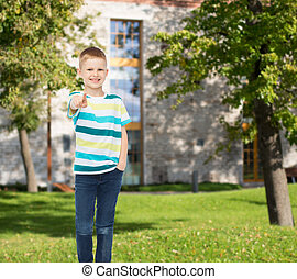 smiling little boy pointing finger at you