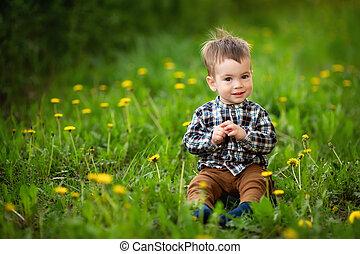 little boy sitting in the flowering meadow