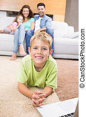 Smiling little boy using laptop on the rug with parents...