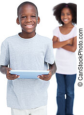 Smiling little boy using tablet PC with his sister behind...