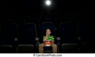 Smiling little boy watching movie in a cinema