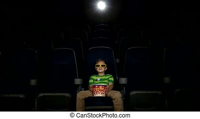 Smiling little boy watching movie in a cinema, 3D glasses
