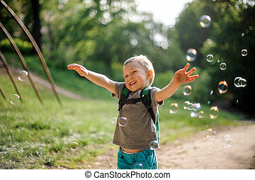 Smiling little boy with soap bubbles in summer park on sunny day