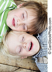 smiling Little brothers lying close together - Portrait of...