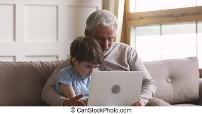 Smiling little child son watching movie with grandfather at ...
