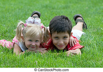 smiling little friends at the park - a little girl and a boy...